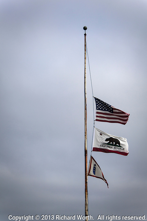 The United States,  California State  and  Lighthouse Service flags fly at half mast, or half staff against a gray, overcast sky.  Image modified, flipped, in software to make the writing on CA flag readable.