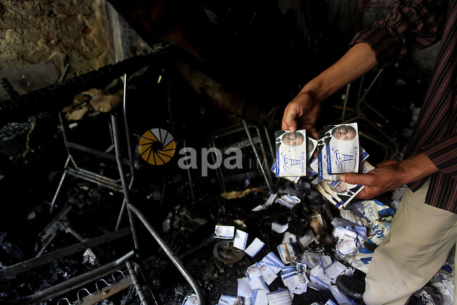A man shows flyers of presidential candidate Ahmed Shafiq at the scene of the burnt campaign headquarters of Shafiq in Cairo May 29, 2012. A group of Egyptian protesters set fire to the headquarters on Monday, the state news agency reported, after the ex-prime minister made it into the second round of the vote. Photo by Ashraf Amra