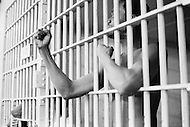 Manhattan, New York City, NY. November 1st, 1972.<br /> A prisoner shaking his fists through the bars of his cell in the Tombs Prison, New York. The prison standing on Center Street and Leonard Street, was built in 1840 with granite from the old Bridewell Prison in City Hall Park.