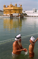 A young boy and his father bathe in the water tank that surrounds the Golden Temple at Amritsar, the holiest of all Sikh shrines.