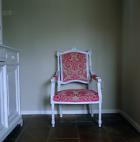 In the kitchen an antique armchair has been covered in beige and strawberry velour