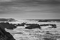On a rocky outcrop, a visitor to California's Pescadero State Beach:  a miniscule silhouette against massive sky and sea.