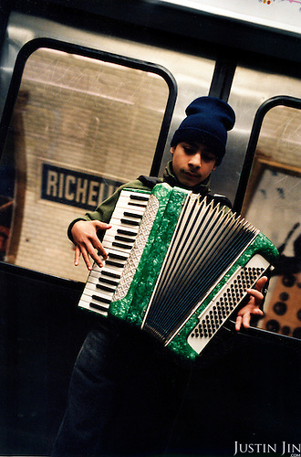 A young Roma busker plays instrument on Paris metro..Picture taken 2005 by Justin Jin