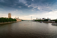 Dramatic cloudy day view of the River Thames and London Eye in London, England.