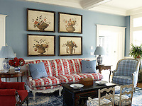 A quartet of framed floral paintings has been arranged above an antique sofa covered in red and white stripes next to an armchair upholstered in a subtle grey tartan