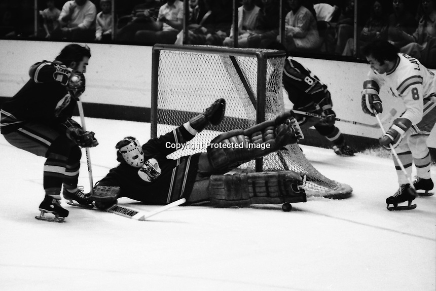 Kansas City Scouts goalie Bill McKenzie makes save on shot by California Golden Seals Brian Lavender. 1975<br />