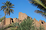 Kasbah Tiffoultoute with palms against blue sky.