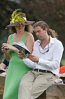 A couple looking over the program prior to race 6 on derby day at Oaklawn.(Justin Manning/Eclipse Sportswire)