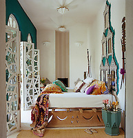 A bespoke wooden bed frame also has a unique headboard made of a series of inlaid Indian mirrors