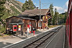 Swiss red Bernina Express trains stop at Surovas train station, on the way to St. Moritz, Switzerland