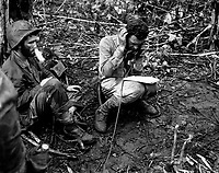 Lt. Col. John Weber, commanding officer of a Marine battalion on Cape Gloucester, sitting on his helmet, receives a report from one of his company commanders.  Pfc. Vincent Miley, looking on, blows cigarette smoke out of his nose.  January 1944. Brenner. (Marine Corps)<br /> Exact Date Shot Unknown<br /> NARA FILE #:  127-N-72050<br /> WAR &amp; CONFLICT BOOK #:  1192