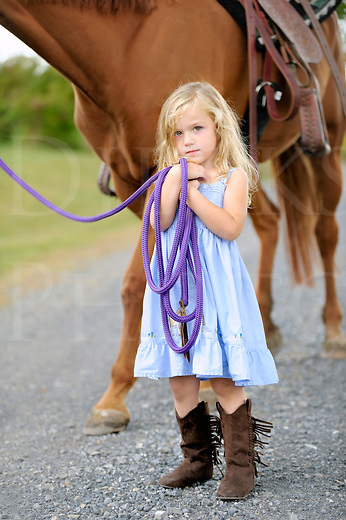 Little blonde girl standing beside a big horse while holding the lead line.