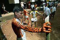 Pulikali performers drying their body paint standing under the sun. Trichur, Kerala, India..Pulikali or Kaduvvakali is a two hundred year old folk dance form, practised mostly in Thrissur and Palghat districts of Kerala. It liberally makes use of forms and symbols of nature that finds expression in its bright, bold body painting and high-energy dance movements. The philosophy of Pulikali is that human and nature are integral parts of each other. So by fusing man and beast in its artistic language, it flamboyantly celebrates the connection. Arindam Mukherjee