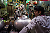 A young shop vendor scoops out biryani while the customer waits at his stall in Nizamuddin, New Delhi, India.