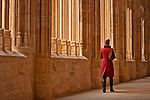 A woman with a red winter coat walks through the halls of the Cloister in the Cathedral of Segovia, built between 1525 and 1577 in the late Gothic style