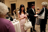"""Newport, California, July 22, 2011 - Contributor Julie Spira, center, checks her phone at The Divorcee Sale at the Pelican Hill Resort in Orange County. Organized by Jill Alexander, the sale offers luxury items most of which from uber-rich divorcees looking to unload their proverbial baggage. The event also donates 25 percent of its profits to breast cancer research...Alexander, who has actually never been married, started The Divorcee Sale this past spring after noticing a trend amongst her friends and colleagues going through divorces. """"Many women have an attachment to these things and they just want to move on,"""" says Alexander. She added that the consignment shops were full and not really offering much in the way of sympathy in the situation. Alexander is different in that she visits the home of the divorcees, often with cakes and tissues, and acts as both a consignor and a confidant. ."""