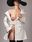 Beautiful young half naked woman wearing a trench coat and a sun hat