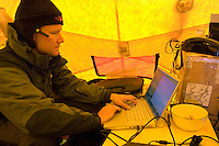 Scientist inside a tent on the Greenland ice sheet studying data on a laptop computer.