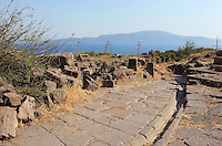 Road from the theatre with drainage channel at Assos, Turkey, with the Aegean Sea in the background. The city was founded from 1000 to 900 BC by Aeolian colonists from Lesbos. Aristotle (joined by Xenocrates) went to Assos, where he was welcomed by King Hermias, and opened an Academy in this city, where he led an influential group of philosophers. Picture by Manuel Cohen
