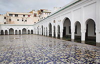 Courtyard of the Mausoleum of Moulay Idriss I, open only to non-muslims, with its tiled floor and horseshoe arch colonnade, Moulay Idriss, Meknes-Tafilalet, Northern Morocco. The mausoleum was rebuilt by Moulay Ismail, 1672-1727, in the 17th century and is the site of an important moussem or pilgrimage festival each summer. The town was founded by Moulay Idriss I, who arrived in 789 AD and ruled until 791, bringing Islam to Morocco and founding the Idrisid Dynasty. His body was moved to a tomb in the mausoleum. Picture by Manuel Cohen