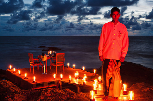 A waiter prepares a table for a ocean side candle light dinner for two at Saman Villas, Aturuwella, Bentota, Sri Lanka.