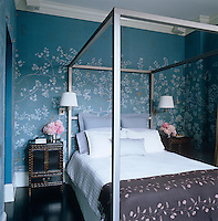A metal framed four-poster bed sits in a bedroom with walls covered in Chinoiserie hand-painted wallpaper by De Gournay