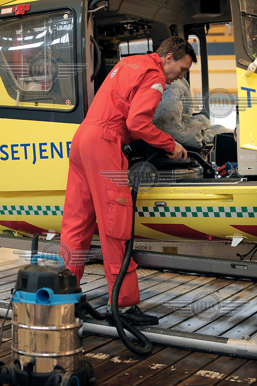 Pilot Morten Jystad  cleaning the helicopter after a mission. Norwegian Air Ambulance base at Dombås.