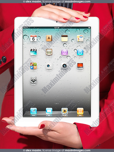 Closeup of a woman in red business suit holding a white iPad in her hands