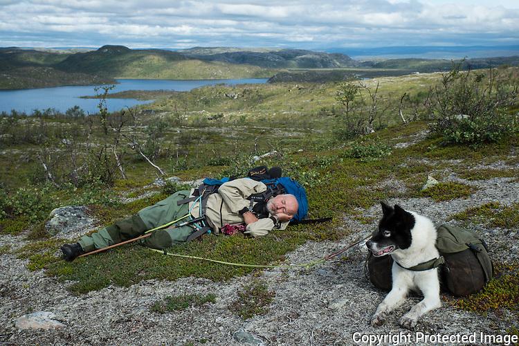 Mann og kløvhund slapper av ved stien mot Karlebotn. ---- Man and dog relaxing.