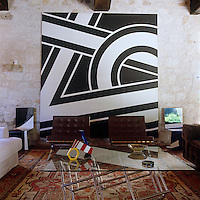 A large black and white abstract painting by Pierre Clerk is propped behind a pair of Barcelona chairs and a modern glass coffee table in the living room
