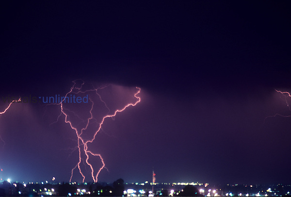 Lightning storm over a city at night.