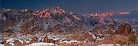 902000021 a panoramic view of dawn alpenglow on mount whitney mount russell and lone pine peak during a clearing snowstorm with a dusting of fresh snow on the eastern sierras and the granite boulders of the alabama hills in the blm protected lands near lone pine kern county california