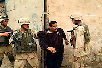 """Baghdad, Iraq, June 2, 2003.US troops often completely misunderstand perfectly benign circumstances for lack of translators and proper training, creating potentially dangerous situations for the Iraqi population they are supposed to protect. Here, a couple of gunshots were fired in the air at the end of a wedding as is customary, US troops parolling the area blocked up a street and tried to break into a house where they wrongly thought the """"shooter"""" had taken refuge, the man being arrested and quite brutally treated, is in fact the owner of the house who keenly offered to open it to prove it was empty..."""