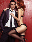 Sexy couple portrait of young man wearing a suit and red-haired woman in lingerie holding him by the necktie on red background