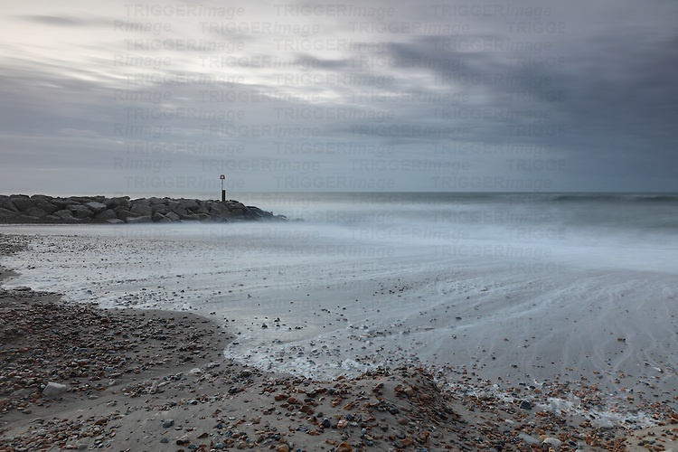 Stone jetty with rough seascape under grey clouds