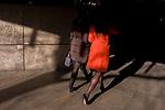 Women walk into dark shadows in Broadgate in the City of London.