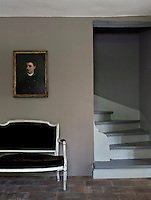 In the entrance hall a stunning composition of texture and colour has been created by the juxtaposition of a black velvet sofa and gilt-framed painting set against a wall painted a simple flat grey