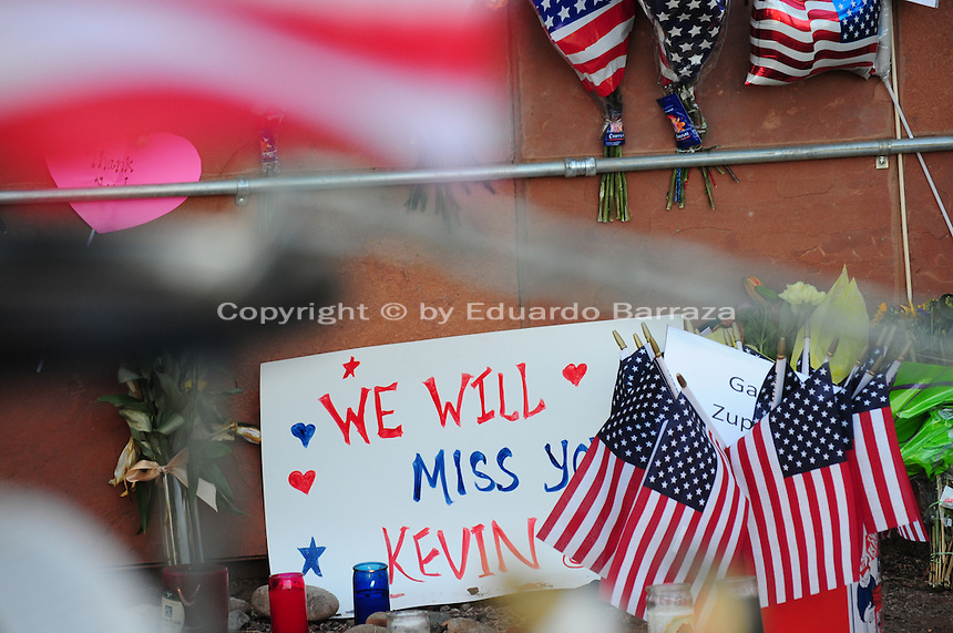 Phoenix, Arizona. July 3, 2013. A small makeshift memorial for the 19 Arizona firefighters who died on June 30 battling the Yarnell Hill wildfire was built outside the Forensic Science Center in Phoenix, where autopsies are being conducted. A sign written by Captain Albert Bandin honors the 19 members of the Granite Mountain Hotshots team who perished fighting a wildfire in the community of Yarnell, Arizona. The remains of the 19 firefighters were taken to the Maricopa County Medical Examiner's Office where this memorial was built for the men who are considered heroes for dying battling the Yarnell Hill Fire 80 miles northwest of Phoenix, Arizona. Photo by Eduardo Barraza © 2013