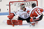 Chris Rawlings (Northeastern - 37) makes a save as Alex Angers-Goulet (RPI - 18) skates in. - The visiting Rensselaer Polytechnic Institute Engineers tied their host, the Northeastern University Huskies, 2-2 (OT) on Friday, October 15, 2010, at Matthews Arena in Boston, MA.