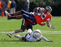 Oct 30, 2010; Charlottesville, VA, USA;   Virginia Cavaliers running back Keith Payne (22) is tackled by Miami Hurricanes linebacker Colin McCarthy (44) and Miami Hurricanes defensive back Vaughn Telemaque (7) during the 1st half of the game at Scott Stadium.  Mandatory Credit: Andrew Shurtleff