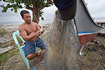 A man repairs a net on Jinamoc Island, part of the municipality of Basey in the Philippines province of Samar that was hit hard by Typhoon Haiyan in November 2013. Known locally as Yolanda, the storm left most of the island's boats, nets, and houses destroyed.  The community received a few new boats from the government, and material for new nets from a media conglomerate. The ACT Alliance has been providing a variety of assistance to survivors, including cash for work and temporary housing, and is planning a long-term rehabilitation program with residents that will include permanent housing, schools, agricultural development, livelihood activities, and water and sanitation facilities.