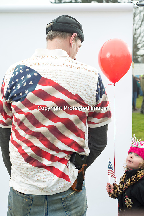 Gary Ehrheart, of Anacortes, speaks with his daughter Ellamina, 4, while attending the Guns Across America rally that drew about 1,500 people to the Washington State Capitol in Olympia Saturday, Jan. 19, 2013.  &quot;I own guns for my enjoyment, for my protection and for the protection of our liberty,&quot; Ehrheart said while wearing a constitution shirt he paid $2.99 for at a local Value Village thrift store recently. Photo by Daniel Berman/www.bermanphotos.com.
