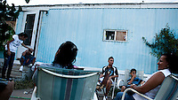 A family sit outside their home in a trailer park in Garden City, Kansas. This is home to many of the migrant workers who have come to the town to work at the Tyson meat packing plant. The Tyson facility kills and processes between five and six thousand beef cattle every day. Kansas dominates the American beef industry, producing 25% of all beef raised in the USA. However, the industry is heavily dependent on cheap immigrant labour.