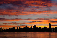 The sky begins to lighten and clouds reflect pre-sunrise color over the Empire State Building and other buildings of the Manhattan skyline.