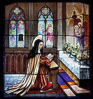 Detail of small stained glass window showing Santa Teresa praying, left side of central nave, Convento de Santa Teresa,(Convent of St Teresa), 1629-36, Avila, Spain, built in Baroque style on the site of St Teresa's birthplace by architect and monk Alonso de san Jose (1600-54). Santa Teresa (1515-82), was a Carmelite nun, canonized 1622. Photograph by Manuel Cohen.