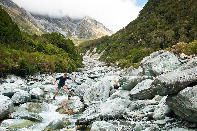Tramper jumping over rocks in Butler River South Branch near Whataroa, South Westland, West Coast, New Zealand