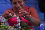 A vegetable merchant feeds her pet parrots while awaiting patrons in San Salvador's central market.