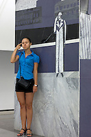 """Moscow, Russia, 20/06/2010..A girl poses beside a mural depicting Svidrigailov's suicide in Crime & Punishment at the just-opened Dostoevsky metro station, the newest in Moscow's underground metro system. The station's opening was delayed by several weeks after psychiatrists claimed the gloomy and violent images in murals depicting scenes from Dostoevsky's novels would make the station a """"mecca for suicides""""."""