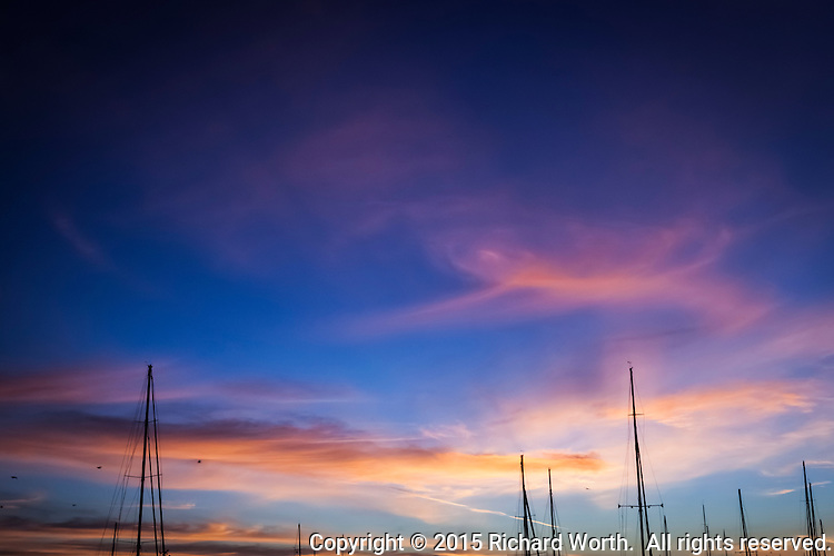 The masts of moored sailboats against a sunset sky of orange and blue.