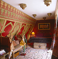 This narrow bedroom has an Indian sofa infront of a Moroccan wall-hanging and Moroccan lanterns punctuating the low ceiling